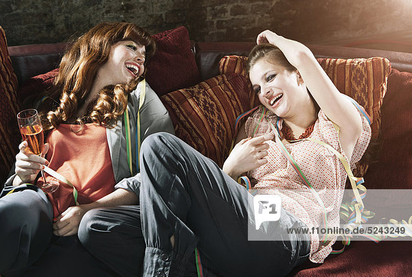 Junge Frauen halten Champagnerglas und ruhen sich auf der Couch aus  lächelnd