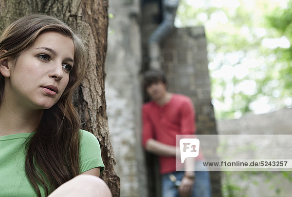Close up of young woman leaning against tree with man in background