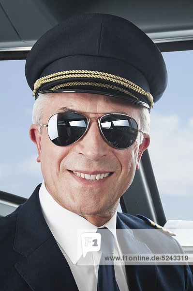 Germany  Bavaria  Munich  Senior flight captain wearing aviation glasses in airplane cockpit  smiling  close up