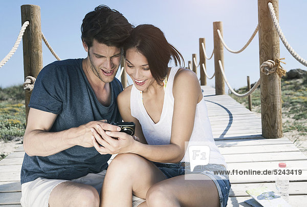 Spain  Majorca  Young couple with camera sitting on boardwalk at beach  smiling