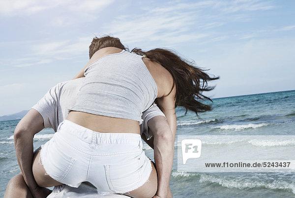 Spanien  Mallorca  Junger Mann mit Frau auf dem Rücken am Strand