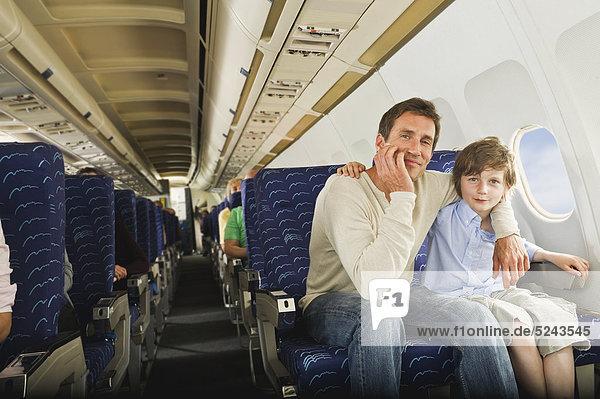 Mann und Junge sitzen zusammen im Economy-Class-Flugzeug