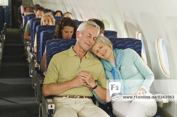 Deutschland  München  Bayern  Passagiergruppe im Economy Class Flugzeug  lächelnd