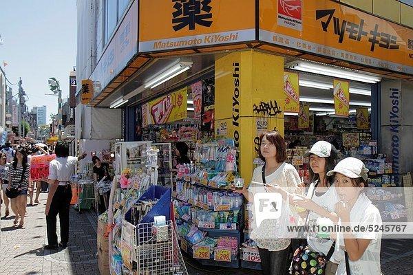 Japan  Tokyo  Harajuku  Takeshita Dori  Street  shopping  shoppers  kanji  hiragana  characters  Japanese and English  Matsumoto Kiyoshi  pharmacy  drugstore  front  entrance  household products  Asian  teen  girl  daughter  woman  mother