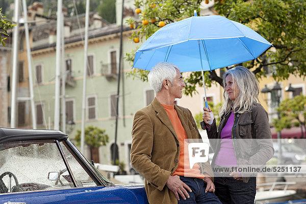 Seniorenpaar mit Oldtimer und Regenschirm am Hafen  Italien  Gardasee