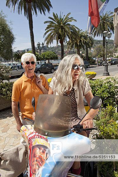 Lachendes Seniorenpaar mit Motorroller  Italien