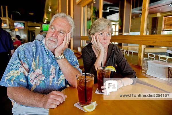 A middle aged couple appeared indifferent to each others´ company over iced tea together in a Long Beach  CA  restaurant