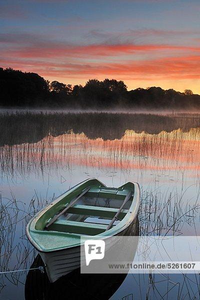 Boot vertäut neben See im Morgengrauen