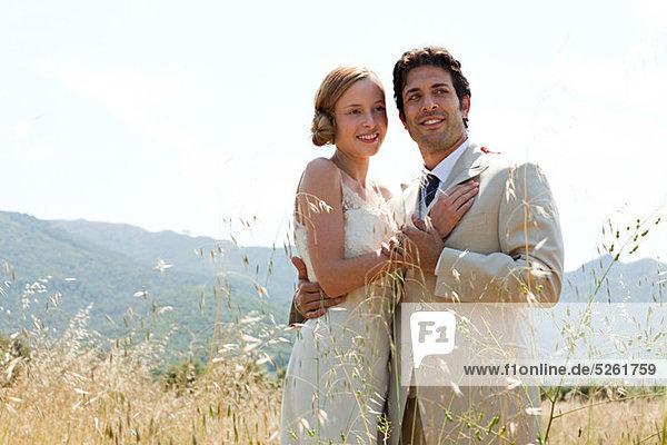 Brautpaar im Feld umarmen Brautpaar im Feld umarmen