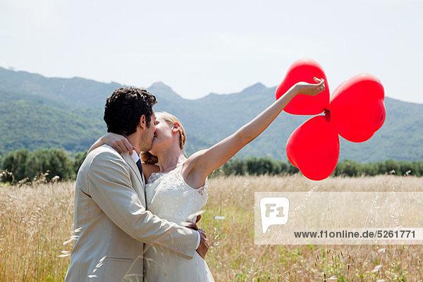 Frischvermähltes Küssen im Feld mit roten Herzballons Frischvermähltes Küssen im Feld mit roten Herzballons