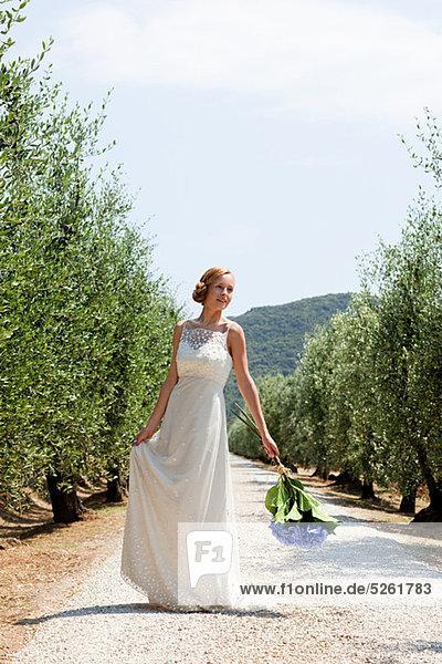 Braut auf der Landstraße mit Blumenstrauß