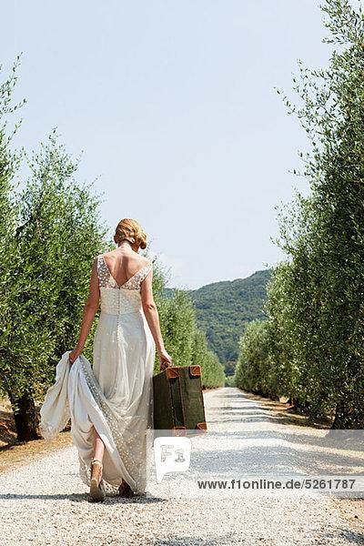 Braut mit Koffer auf der Landstraße