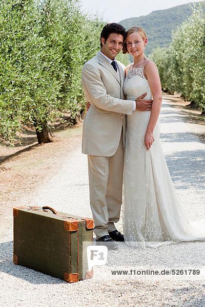 Jungvermählten auf Landstraße mit Koffer Jungvermählten auf Landstraße mit Koffer