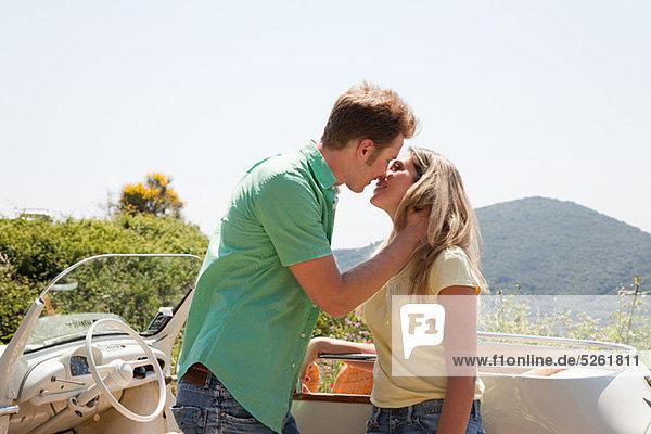 Junges Paar von convertible Car küssen