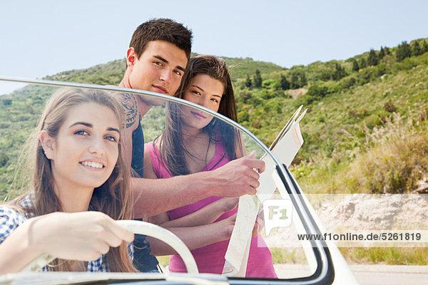 Junge Freunde mit convertible Car Blick auf Karte