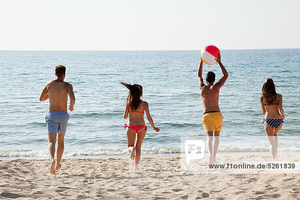 Vier Personen spielen mit Beachball am Strand