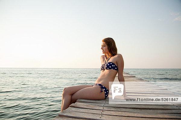 Junge Frau sitzt auf Bootssteg  Portrait