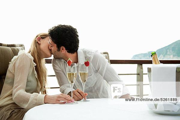 Junges Paar küssen mit Champagner