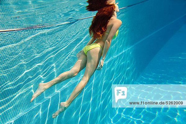 Junge Frau schwimmt unter Wasser im Schwimmbad