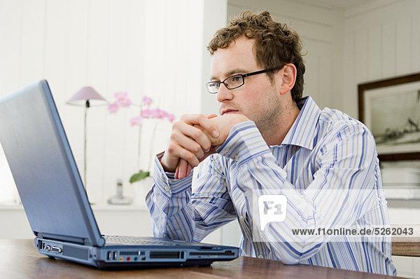 Mann mit Laptop in der Küche