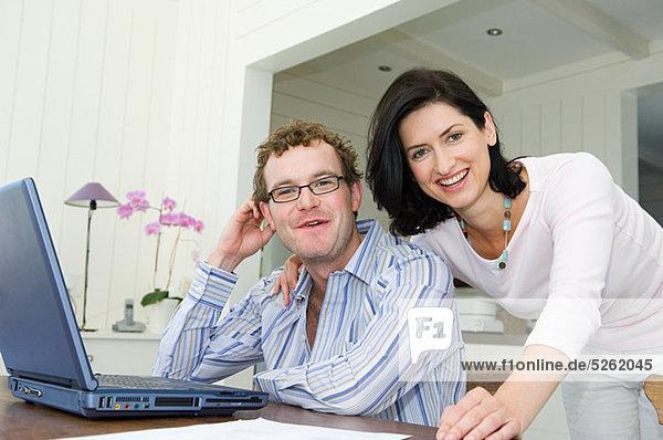 Paar mit Laptop in Küche