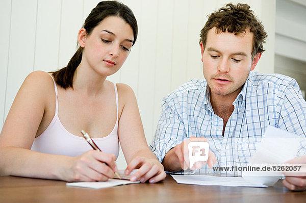 Paarplanung Hausfinanzen  Frau stellt Scheck aus