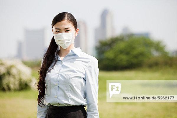 Junge Geschäftsfrau mit Verschmutzungsmaske
