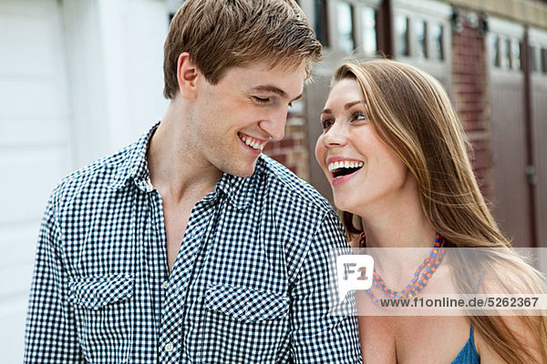 Young couple laughing outdoors