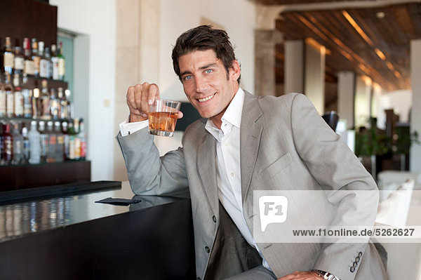 Confident man at a bar with drink
