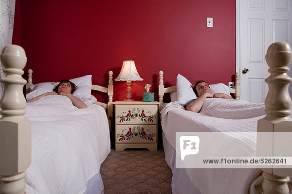 Junges Paar in Einzelbetten wach liegend