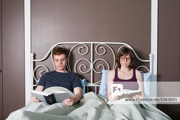 Junges Paar liest im Bett