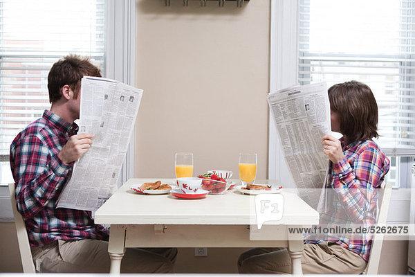 Junges Paar beim Zeitungslesen am Küchentisch