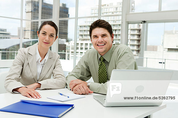 Geschäftsmann und Geschäftsfrau treffen sich im Büro mit Laptop