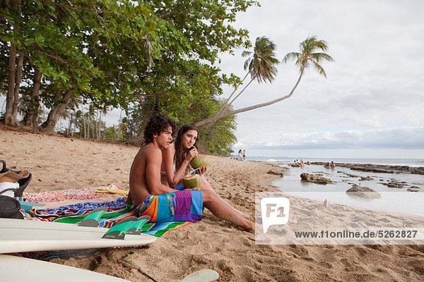 Junges Paar sitzt am Strand und trinkt Kokosnussmilch.