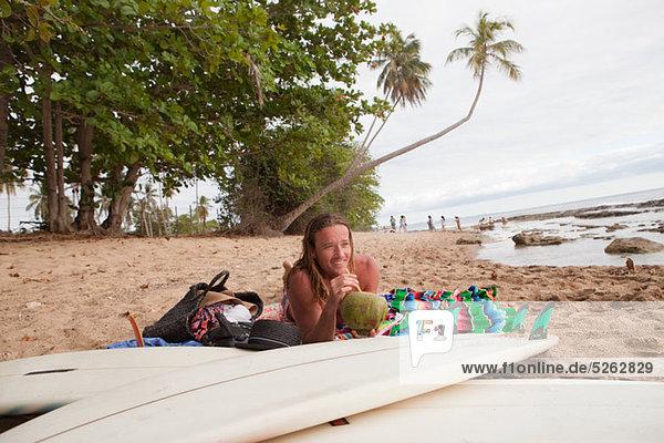 Mann liegen am Strand Kokosmilch trinken
