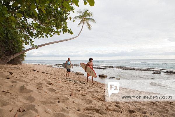 Zwei Männer tragen Surfbretter am Strand