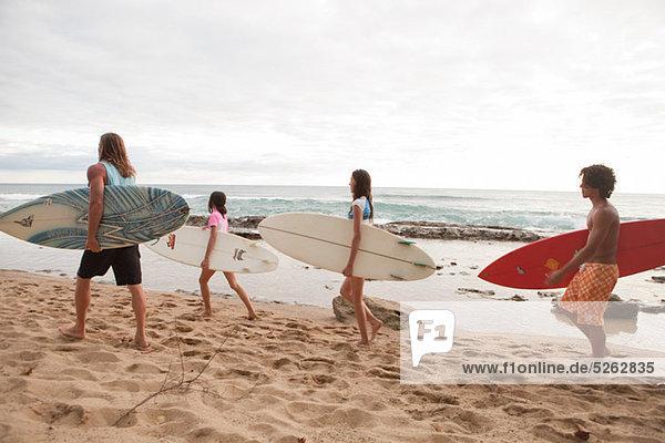 Vier junge Freunde mit Surfbrettern am Strand