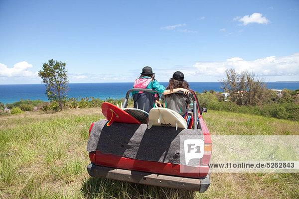 Aus Straßenfahrzeug Fahrt Richtung Strand mit zwei Frauen auf der Rückseite