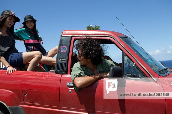 Drei junge Freunde aus Straßenfahrzeug auf Urlaub fahren