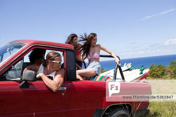Vier junge Freunde aus Straßenfahrzeug auf Urlaub fahren