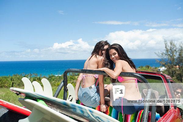 Junge Frauen in aus Straßenfahrzeug mit Surfbretter