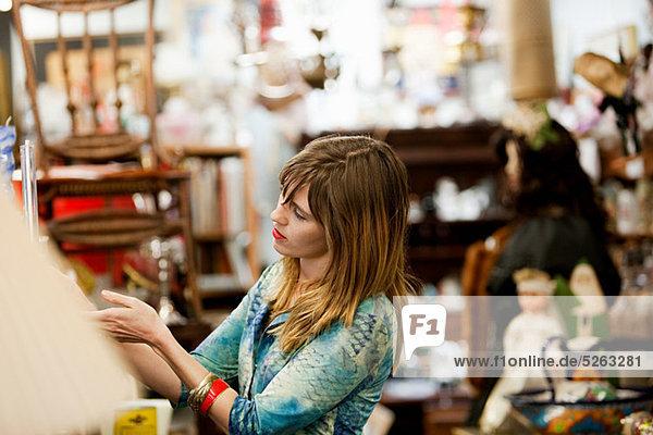 Frau inspiziert Artikel für den Verkauf im Antiquitätenladen