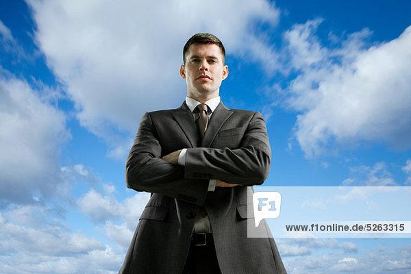 Geschäftsmann mit gekreuzten Armen  niedriger Winkel