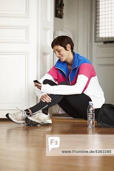 Handy sitzend junge Frau junge Frauen benutzen Boden Fußboden Fußböden Kurznachricht