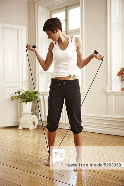 Woman stretching with skipping rope