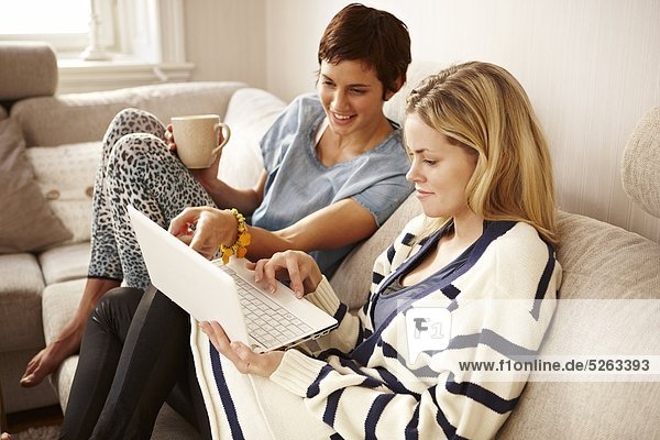 Two women sitting on sofa and using laptop