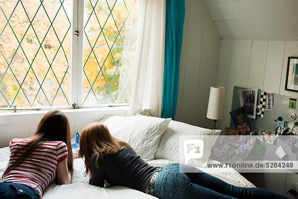 Two teenage girls lying on bed