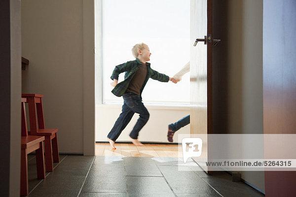 Zwei Kinder rennen an der Tür vorbei
