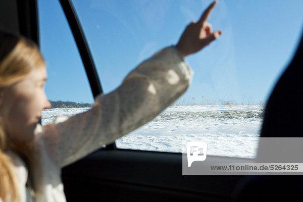 Junge Mädchen  die zeigen über die Autofenster
