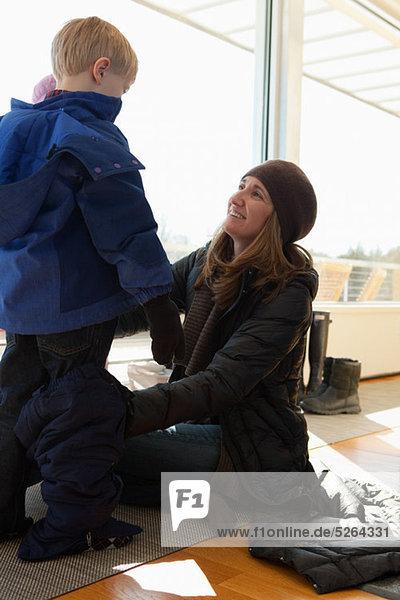 Junge zieht sich in Winterkleidung an  Mutter hilft mit